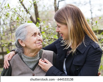 Picture of an elderly woman with cheerful caregiver outdoor in the garden, springtime