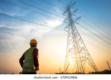 Picture of an electrical engineer standing and watching at the electric power station to view the planning work by producing electricity at high voltage electricity poles. - Shutterstock ID 1709519806