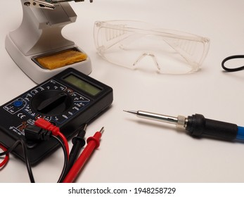 Picture of electronic repairing tools, consist of PCB holder stand, soldering iron, multimeter and protective eyeglass. Shoot on a white isolated background