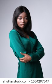 The picture of elegant african woman in dark green dress looking at the camera.