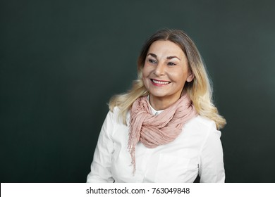 Picture of elegant beautiful elderly 60 year old woman with blonde loose hair and charming smile posing in studio, looking sideways with interest, smiling, showing her perfect white healthy teeth