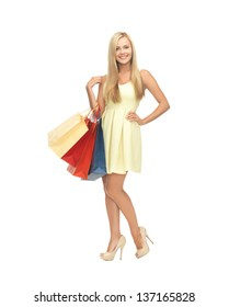 picture of elegant woman with shopping bags in dress and high heels.