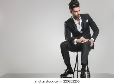 Picture of an elegant young man in tuxedo sitting on a stool, looking away from the camera while holding one hand on his knee.
