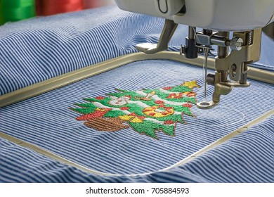 Picture of embroidery machine in close up shot and complete christmas tree design on fabric