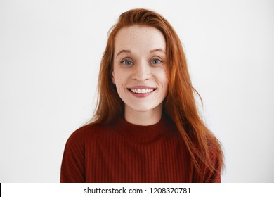Picture of emotioanl attractive young woamn with long red hair smiling cheerfully, having excited or impatient look, staring at camera with eyes popped out, raising eyebrows. Human facial expressions