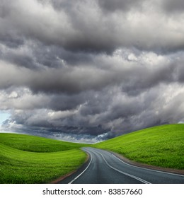 picture of empty road leading toward horizon and cloudy sky