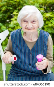 Picture of energized elderly woman doing sport exercises outdoor in the garden, holding pink dumbbells