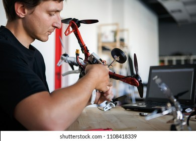 Picture of engineer mending square copter at table