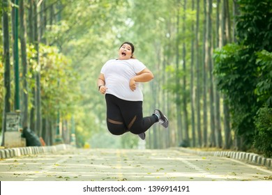 Picture of an excited fat woman leaping on the road while wearing sportswear