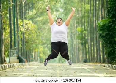 Picture of excited fat woman wearing sportswear while jumping on the road