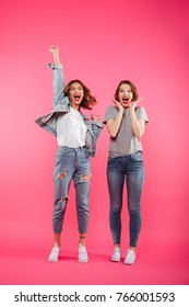 Picture of excited two ladies friends standing isolated over pink background. Looking camera.