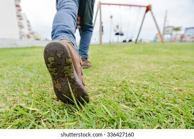 Picture of exciting boy running on children playground. Closeup of leg and boot sole on green grass outdoor background.
