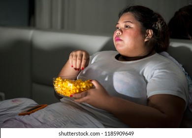 Picture of fat woman eating a bowl of popcorn during watching television in the bedroom. Unhealthy lifestyle concept