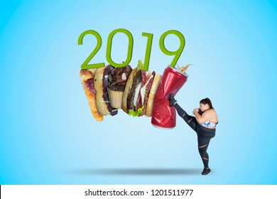 Picture of fat woman kicking soft drink and fast food with number 2019