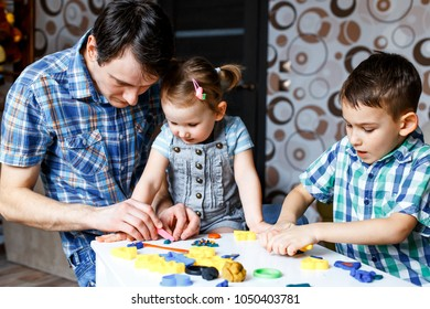 Picture of a father, daughter and son playing with color play dough and cutters. Having fun with colorful modeling clay. Creative kids molding at home. Children play with plasticine or dough.