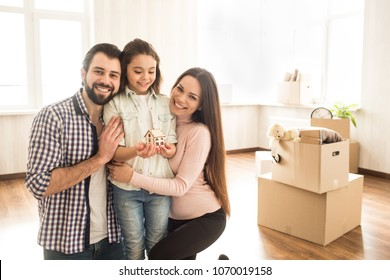A picture of father, mother and their child standing in a bright room. Parents are hugging their child and smiling while girl is holding a wood toy house and looking at it.