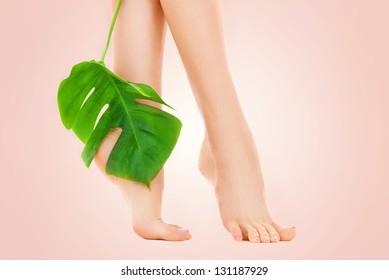 picture of female feet with green leaf over beige background
