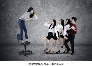 Picture of female leader shouting with a megaphone to her teamwork while standing on the chair
