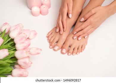 Das Bild der weiblichen Beine und Hände nach Pediküre und Maniküre. Die Beine sind von rosafarbenen Tulpen und Kerzen umgeben.