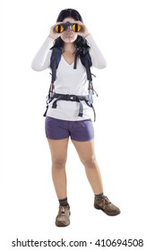 Picture of female traveler carrying hiking bag and using binoculars in the studio, isolated on white background