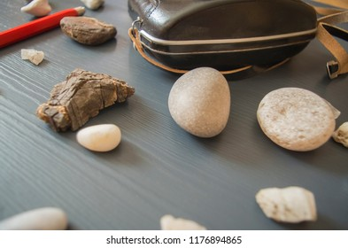 A picture with a few smooth stones from the sea and the sharp one from the mountains. There is a bright red pen for drawings behind the stones and a vintage photo camera in a black case. Nice colors.