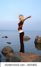 picture of fit girl meditating at the seashore
