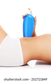A picture of a fit woman holding lotion over her belly