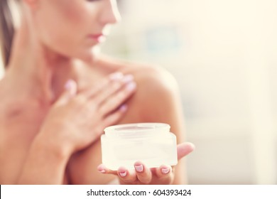 Picture of a fit woman holding lotion over her body