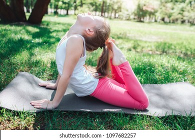 A picture of flexible girl reaching her head with the end of her legs. Sh is doing some exercises outside in park. Yoga and Pilates Concept.