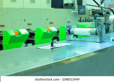Picture of flexographic printing press in background, print sample, magnifying glass and printing roll on working bench. Photo of rotary / flexo press machine. Concept of preparation for quality check