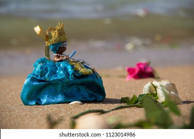 Picture Flowers on the beach sand and a doll representing iemanjá