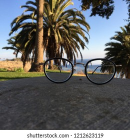 Picture of focal focus behind the lens with blurred background. Eyeglasses sat on the stone the focal picture is the view that look through the lens with blurred palms tree and ocean behind it