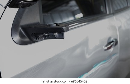 A picture focused on a front door and a broken wing mirror of a broken bronze car parking in a garage