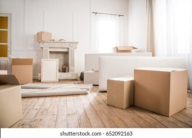 Picture frame and cardboard boxes in empty room, relocation concept