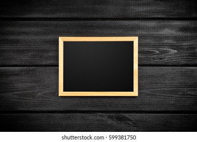 Picture frame on a black wooden wall