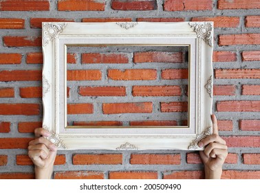 picture frame on hand , brick wall