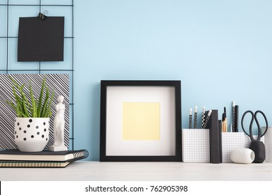 Picture frame on a stylish student desk with a blue wall.