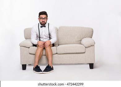 Picture of frightened or shy handsome hipster man sitting on sofa or couch while posing isolated on white background in studio. Emotions concept.
