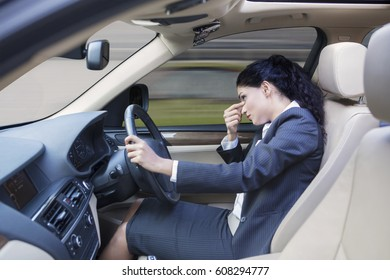 Picture of a frustrated Indian businesswoman driving a car while massaging her forehead