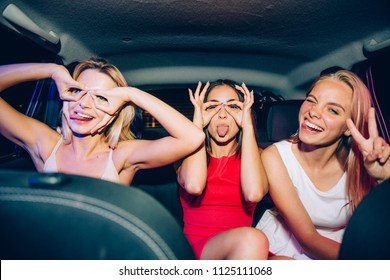 A picture of funny girls making funny figures aroung their eyes. They are showing uo their tongues. One of them is showing piece symbol with her fingers.