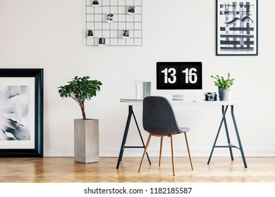 Picture gallery and a concrete planter in a simple home office interior for a freelancer professional with a computer screen mock-up. Real photo.