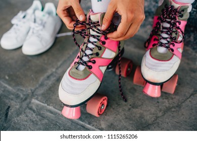 A picture of girl lying laces on her pink rollers. She has changed her white shoes to this funny rollers. Girl is almost ready to rollerblading.