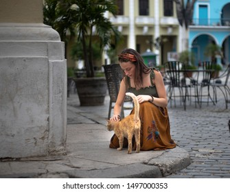 Picture of girl petting a cat in Old Havana, Cuba. Taken with a Canon 5D Mark IV and a Canon 50mm lens.