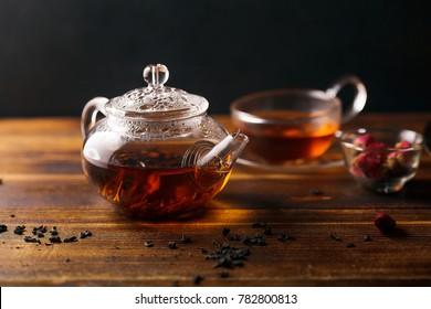 Picture of glass teapot with cup of black tea and golden tray on wooden table. Overhead view, copy space.