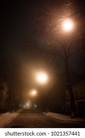 Picture of gloomy night with street lights and fog. Low light image.