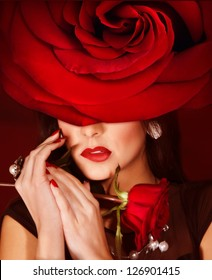 Picture of gorgeous woman wearing fashionable red roses hat, closeup portrait of brunette female with stylish makeup and flower on head, luxury beauty salon, Valentine day, style and fashion concept