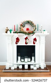 A picture of a great white fireplace decorated with many candles, green pine wreaths and bright red Christmas socks.