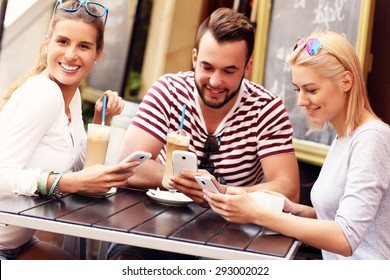 A picture of a group of friends resting in an outdoor cafe and using smartphones