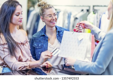 Picture of group of happy friends shopping for clothes in mall