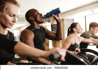Picture of group of multiethnic sports strong people make sport exercise with spinning bicycles drinking water.